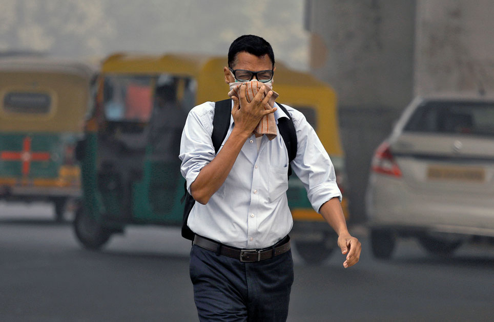Man covers his face as he walks to work in Delhi.