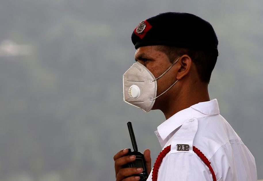 A traffic policeman wearing a mask controls the traffic at a busy road on a smoggy morning in New Delhi.