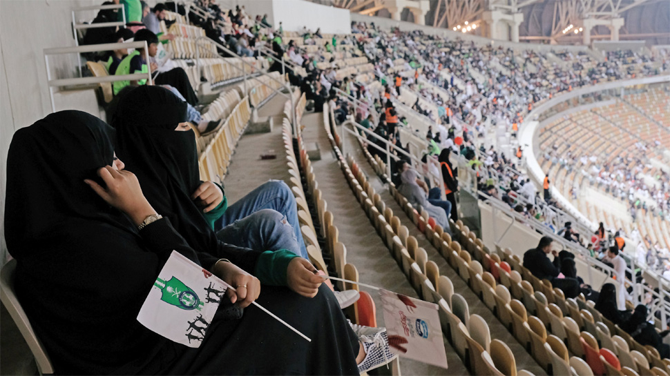 Saudi women watch the soccer match between Al-Ahli against Al-Batin at the King Abdullah Sports City in Jeddah