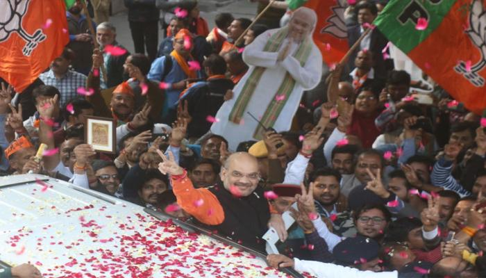 BJP President Amit Shah flashes victory sign as he is welcomed on his arrival at the party headquarters